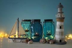 Magisches Weckgläser whith Kerzenlicht und hölzernes Boot im Regal Verrostete, alte, symbolische Kette von einem Anker mit Booten Stockfotos