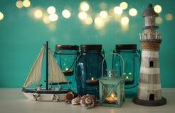 Magisches Weckgläser whith Kerzenlicht und hölzernes Boot im Regal Verrostete, alte, symbolische Kette von einem Anker mit Booten Lizenzfreies Stockbild