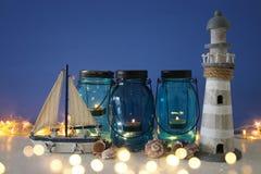 Magisches Weckgläser whith Kerzenlicht und hölzernes Boot im Regal Verrostete, alte, symbolische Kette von einem Anker mit Booten Lizenzfreie Stockfotos