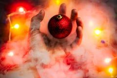 Magisches Weihnachtskonzept Eine merkwürdige frei geschwebte Weihnachtsverzierung fliegt weg von der Hand eines Mannes stockfotografie