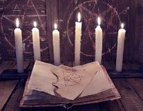 Magisk bok med pentagram- och ondskastearinljus för ockult ritual fotografering för bildbyråer