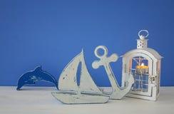 Magisk lykta med stearinljusljus och träfartyget på hyllan Nautiskt begrepp royaltyfria foton