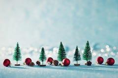 Magisk miniatyrvinterunderlandbakgrund Vintergröna träd, sörjer kottar och röda julstruntsaker på skinande blå bakgrund royaltyfria foton