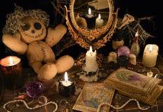 Magisk ritual med voodoodockan, spegeln och tarokkort arkivbild