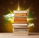 Magiska böcker med strålen av magiska ljus och färgrika moln Royaltyfri Bild