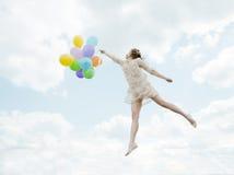 Magiskt älskvärt flickaflyg i himlen med ballonger Arkivfoto