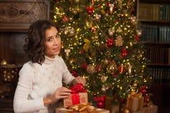 Magiskt ögonblick av jul Flickan öppnar överraskninggåvan för Christma Royaltyfria Foton
