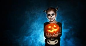 magiskt skelett med pumpa behandla som ett barn flickan i dräkt till halloween Arkivbilder