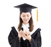 Magistrant/magistrantka używa mądrze telefon Obrazy Stock
