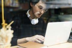 Maglia con cappuccio d'uso del giovane ragazzo asiatico facendo uso del computer portatile digitale Fotografie Stock