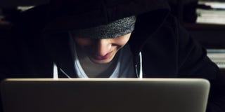 Maglia con cappuccio d'uso del giovane ragazzo asiatico facendo uso del computer portatile digitale Fotografia Stock Libera da Diritti