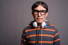 Maglia con cappuccio d'uso e cuffie del giovane uomo asiatico del nerd contro grigio fotografia stock libera da diritti