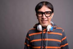 Maglia con cappuccio d'uso e cuffie del giovane uomo asiatico del nerd contro grigio immagini stock libere da diritti