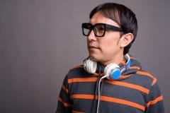 Maglia con cappuccio d'uso e cuffie del giovane uomo asiatico del nerd contro grigio fotografia stock