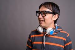 Maglia con cappuccio d'uso e cuffie del giovane uomo asiatico del nerd contro grigio fotografie stock