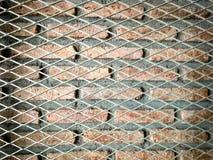 Maglia e muro di mattoni d'acciaio Fotografie Stock