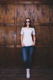Maglietta bianca d'uso della donna davanti alla parete di legno Immagine Stock