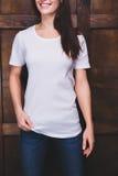 Maglietta bianca d'uso della donna davanti alla parete di legno Fotografia Stock