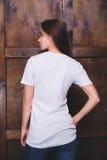 Maglietta bianca d'uso della donna davanti alla parete di legno, vista posteriore Immagine Stock Libera da Diritti