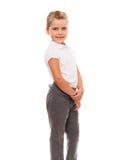 Maglietta bianca d'uso e pantaloni della bambina allegra isolati sopra Fotografia Stock Libera da Diritti