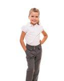 Maglietta bianca d'uso e pantaloni della bambina allegra isolati sopra Fotografia Stock