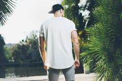 Maglietta dell'uomo muscolare barbuto della foto, cappuccio di snapback e shorts in bianco bianchi d'uso nell'ora legale Parco ve Fotografie Stock