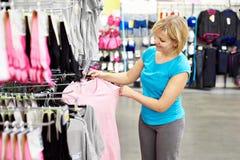 Maglietta felice di acquisto della donna in negozio Immagini Stock Libere da Diritti