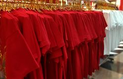 Magliette rosse e bianche che appendono sullo scaffale immagini stock libere da diritti