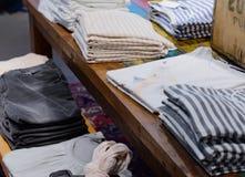 Magliette su uno scaffale dei vestiti fotografia stock