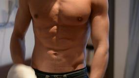 Maglione adatto di apertura dell'uomo dei giovani sul torso muscolare nudo stock footage