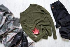 Maglione cachi, jeans neri e una sciarpa Foglia di acero rossa concetto alla moda Fotografia Stock Libera da Diritti