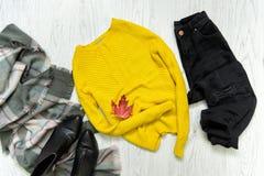 Maglione giallo, jeans neri e sciarpa Foglia di acero rossa concetto alla moda Immagine Stock