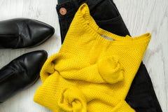 Maglione giallo, jeans neri e stivali concetto alla moda Fotografie Stock