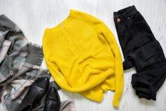 Maglione giallo, jeans neri, stivali e sciarpa Concep alla moda Fotografia Stock