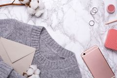 Maglione grigio accogliente con il telefono cellulare ed il fiore del cotone su un fondo di marmo immagine stock libera da diritti