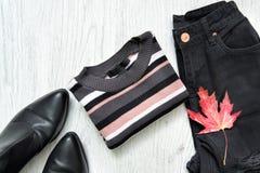 Maglione a strisce, jeans neri, stivali e foglia di acero rossa concetto alla moda Immagine Stock