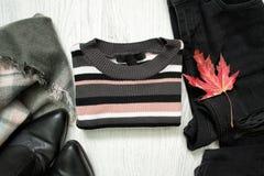 Maglione a strisce, jeans neri, stivali e foglia di acero rossa fashiona Immagini Stock Libere da Diritti