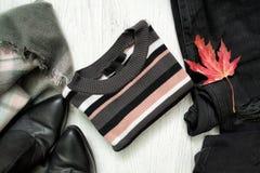 Maglione a strisce, jeans neri, stivali e foglia di acero rossa fashiona Fotografia Stock Libera da Diritti