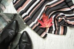 Maglione a strisce, stivali neri e foglia di acero rossa Raggiro alla moda Immagine Stock Libera da Diritti