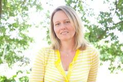 Maglione sveglio di colore giallo della donna all'aperto immagine stock