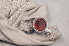 Maglione tricottato pastello caldo accogliente lungo una tazza di tè sul fondo bianco latteo della pelliccia Superi il concetto d fotografia stock