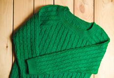 Maglione tricottato verde su un fondo di legno Immagini Stock