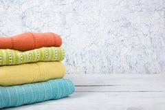 Maglioni tricottati della lana Il mucchio dell'estate tricottata copre su fondo di legno, maglioni, lavori o indumenti a maglia,  Immagini Stock