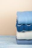 Maglioni tricottati della lana Il mucchio dell'inverno copre su fondo di legno giallo, lavori o indumenti a maglia, spazio per te Immagini Stock