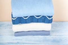 Maglioni tricottati della lana Il mucchio dell'inverno copre su fondo di legno giallo, lavori o indumenti a maglia, spazio per te Fotografie Stock