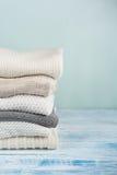 Maglioni tricottati della lana Il mucchio dell'inverno copre su fondo di legno verde, lavori o indumenti a maglia, spazio per tes Fotografia Stock