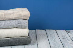 Maglioni tricottati della lana Il mucchio dell'inverno tricottato, autunno copre su fondo blu e di legno, maglioni, lavori o indu Fotografie Stock Libere da Diritti