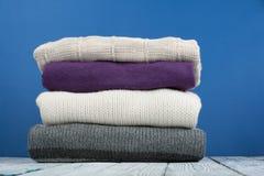 Maglioni tricottati della lana Il mucchio dell'inverno tricottato, autunno copre su fondo blu e di legno, maglioni, lavori o indu Fotografie Stock