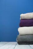 Maglioni tricottati della lana Il mucchio dell'inverno tricottato, autunno copre su fondo blu e di legno, maglioni, lavori o indu Immagini Stock