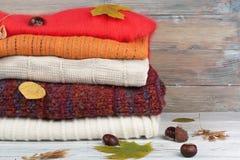 Maglioni tricottati della lana Il mucchio dell'inverno tricottato, autunno copre su fondo rosso e di legno, maglioni, lavori o in Immagini Stock